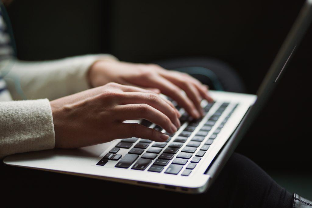 dłonie piszące na laptopie