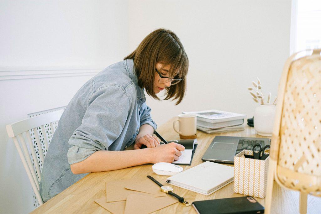 pisząca kobieta przy biurku